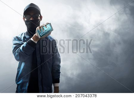 Unknown hacker holding mobile phone on smoke background