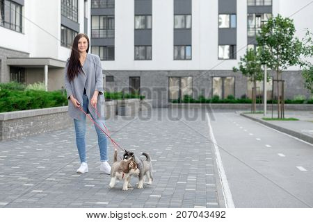 Portrait of happy female strolling with her pet at leisure.
