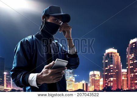 Unknown hacker using mobile phone on the city