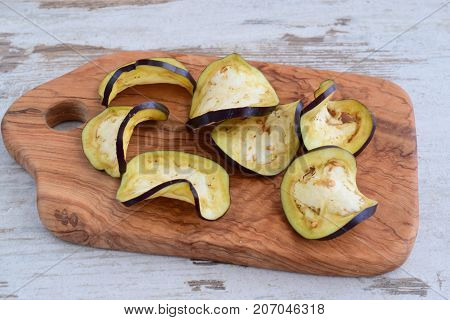 Slices of aubergine on an olive wood cutting board. Step by step cooking.