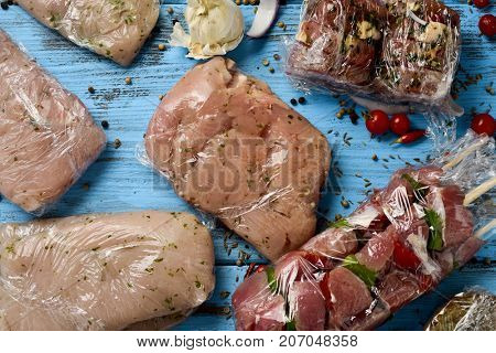 high-angles shot of a blue rustic wooden table, with different packages of raw meat, such as turkey skewers, pork medallions, or slices and chicken breasts wrapped in plastic, ready to be frozen