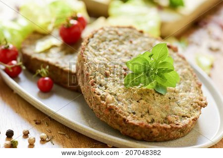 closeup of some veggie burgers made with eggplants and other vegetables in a plate, placed on a rustic wooden table