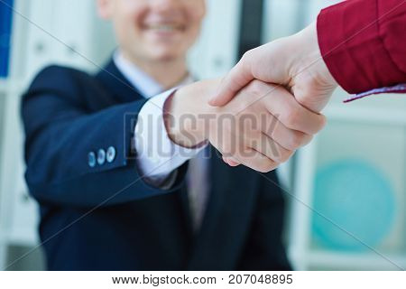 Businessman and woman shake hands as hello in office closeup. Close-up of two young business persons shaking hands with smile while sitting at office.