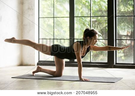 Young attractive woman practicing yoga, standing in Bird dog exercise, Donkey, Kick pose, working out, wearing sportswear, black shorts and top, indoor full length, home interior background
