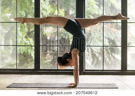 Young woman practicing yoga, standing in Adho Mukha Vrksasana exercise, handstand, Downward facing Tree pose, working out, wearing sportswear, black shorts, top, indoor full length, home background