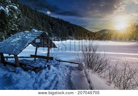 day and night time change concept in winter spruce forest with wooden bower. beautiful mountainous landscape near snow covered frozen lake with sun and moon