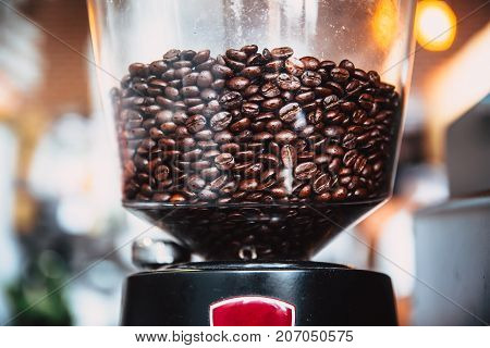 fresh dark roasted arabica coffee bean in electric coffee grinder machine in the cafe