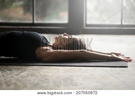 Young attractive woman practicing yoga at home. Doing stretching exercise lying back on mat, tension release pose, relaxing entire body muscles, calms the mind, indoor close up image, floor background