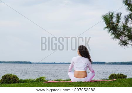 Pregnant yoga. Woman doing different exercises in park on the grass breathing stretching statics. Forest and river on background. Girl is sitting with her back.
