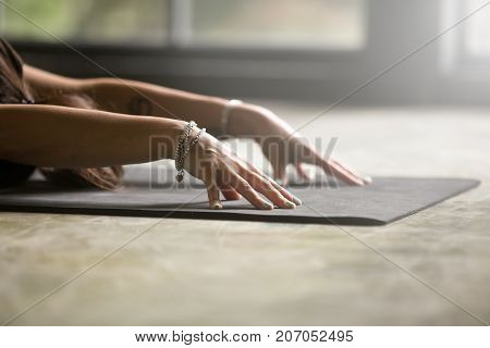 Close up of female hands, arms out in front, palms down, woman practicing yoga at home, sitting in Child exercise, Balasana pose, working out wearing wrist bracelets, indoor close up, floor background