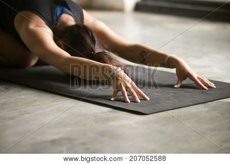 Close up of female hands, pressing into the mat, woman practicing yoga at home, sitting in Child exercise, Balasana pose, working out, wearing wrist bracelets, indoor close up, floor background