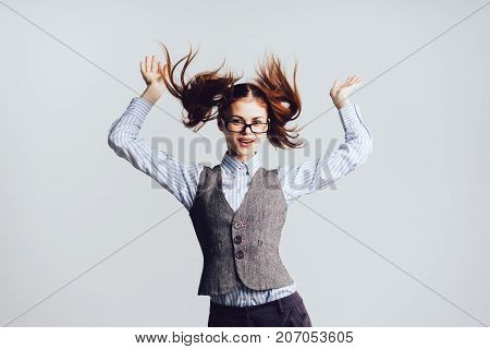 funny girl with two ponytails and with glasses jumps, isolated on white background
