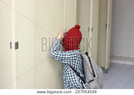 Masked thief with a balaclava sneaking in toilet. Social risk concept.