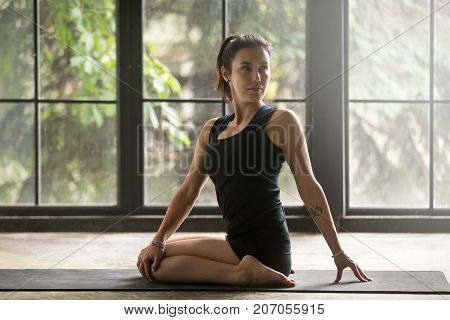 Young attractive woman practicing yoga at home, sitting in Hero exercise, Revolved variation of pose, working out, wearing sportswear, black shorts and top, indoor full length, studio background