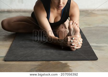 Young sporty woman practicing yoga, stretching in Janu Sirsasana exercise, Head to Knee Forward Bend pose, working out, wearing sportswear black shorts and top, indoor close up, home studio background