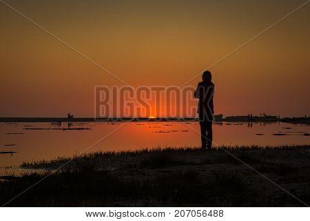 The sun dips below the horizon as an onlooker watches