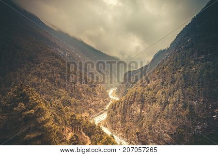 Mountain Valley. Beautiful river landscape and mountain forest in Nepal. Trekking route to Everest Base Camp, Himalayas. Travel, holidays, recreation. Autumn nature landscape. Retro vintage toning
