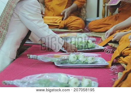Unidentified people give the offering dedicated to the monks in temple