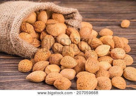 almonds nuts in bag on wooden backgroun