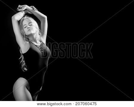 beautiful young woman show her slim body on black background with copy space, monochrome