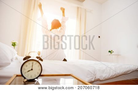 Alarm clock black is placed on a white bed in bedroom in front of woman is wake up with warm emotions with the Sun in the morning.