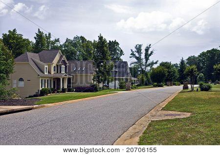 A row of houses along a suburban neighborhood street. poster