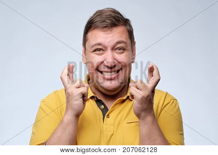 Attractive fat man in yellow t-shirt waiting for special moment and crossing fingers. Be happy, win in lottery or make a wish