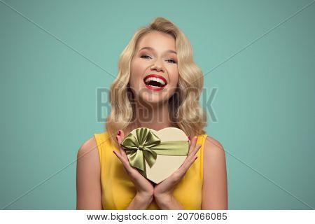 Young smiling woman holding gift. Valentine day.