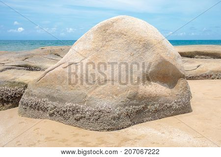 Big rock or stone on the sand beach.