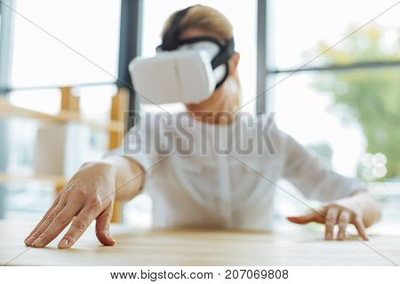 Technological advances. Selective focus of a female hand touching the table surface while being in 3d reality