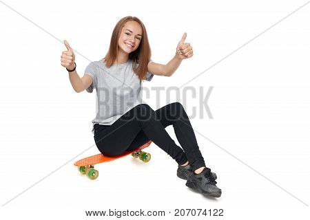 Teen girl in full length sitting on skate board giving double thumb up, isolated on white background