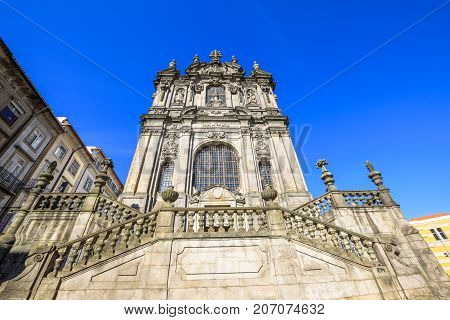 Prospective view of baroque facade of Church of Clerigos or Igreja dos Clerigos in historic center of Porto, Porgugal, one famous panoramic viewpoint of city. Sunny day in the blue sky.