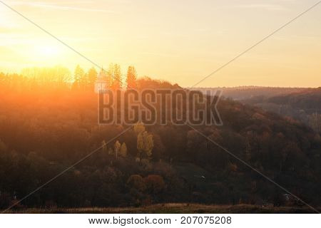 Landscape Of Old Solitary Church On The Hill With Autumn Forest During The Sunset