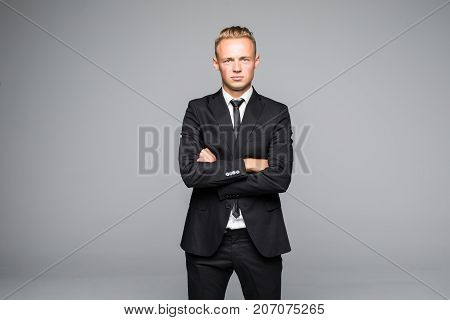 Portrait Of A Confident Businessman With Arms Folded Over Gray Background. Looking At Camera
