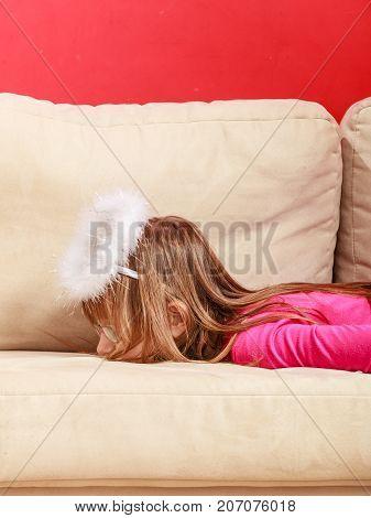 Bored Girl Dressed As An Angel Lying On Sofa