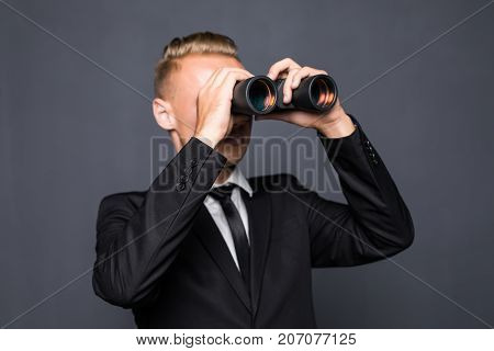 Handsome Young American Businessman Using Binoculars In Office On Gray Background