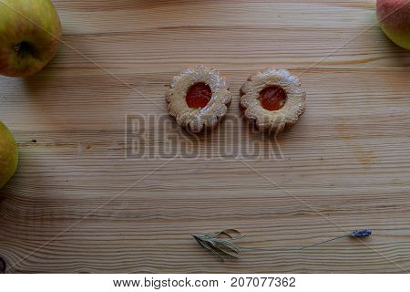 Two cookies whit fresh apples at the wooden background
