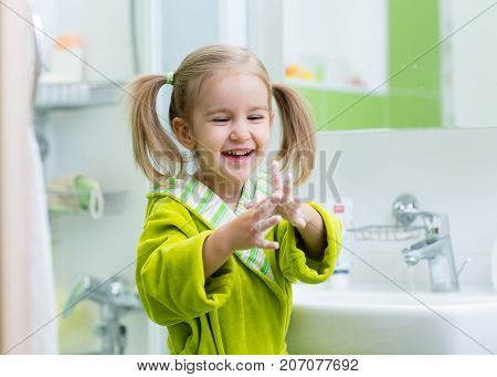 child girl washing and showing soapy hands