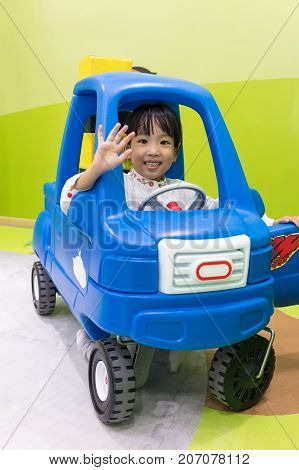 Asian Chinese Little Girl Driving Toy Car
