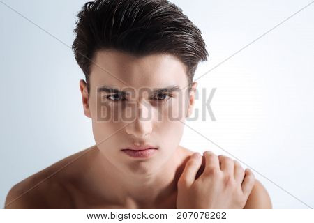 My portrait. Delighted male person pressing lips and raising eyebrows while touching his naked shoulder