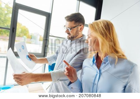 Smile and do. Attentive bearded man holding diagrams while checking documents, standing near his partner