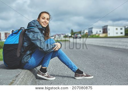 woman traveler with backpack seats on the road and waiting for the car will stop