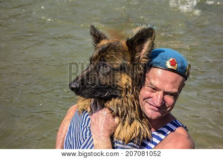 Moscow Russia - August 02 2017: Day of the Airborne Forces a paratrooper in a blue beret closeup embraces a dog in a vest.