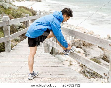 Female runner tying shoelace at the seaside