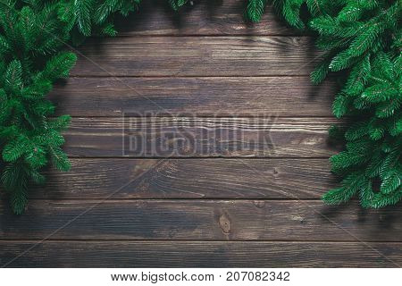 Christmas or fir backgrounds. Wooden background with fir-tree on the edge. Layout for Christams design