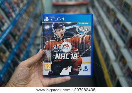 Bratislava, Slovakia, october 2 2017: Man holding NHL 18 videogame on Sony Playstation 4 console in store
