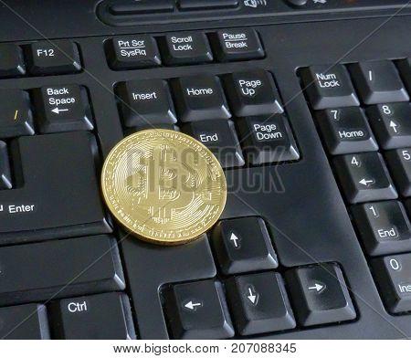 golden bitcoin on black keyboard close up