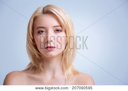 Having disdain. Serious blonde looking straight at camera and having nice haircut while posing over grey background