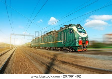 Locomotive Electric With A Freight Train At High Speed Rides By Rail Road.