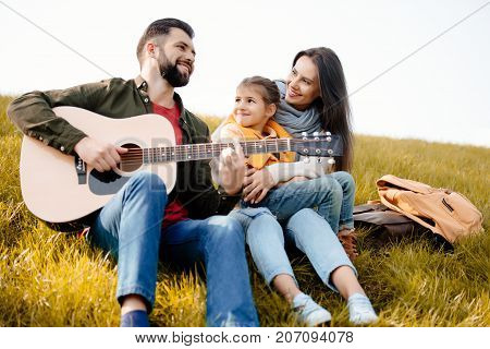 Family Relaxing On Grassy Hill